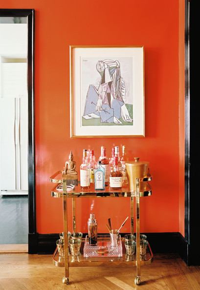 A small brass bar cart against an orange painted wall