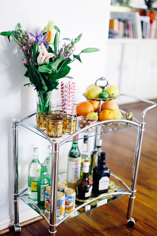 A small bar cart with a vase and vintage glasses
