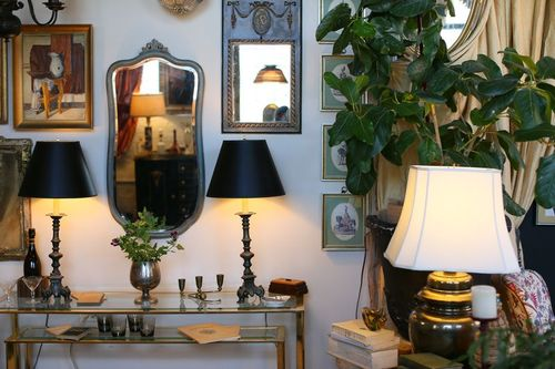 Twin black lamps on glass console table, and assorted decor hanging on wall
