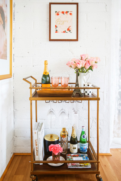 A brass bar cart with pink vintage glasses and flowers