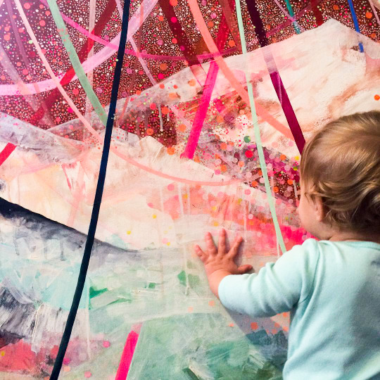 baby in front of abstract art