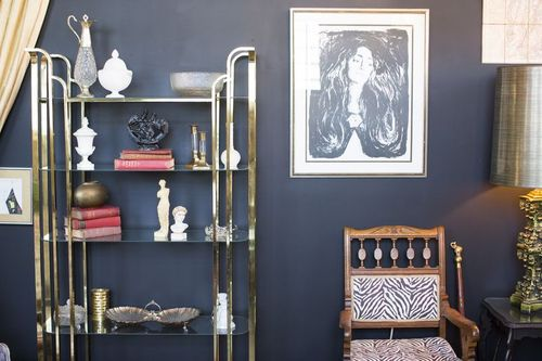 Glass gold trimmed shelving, zebra printed accent chair, and golden lamp