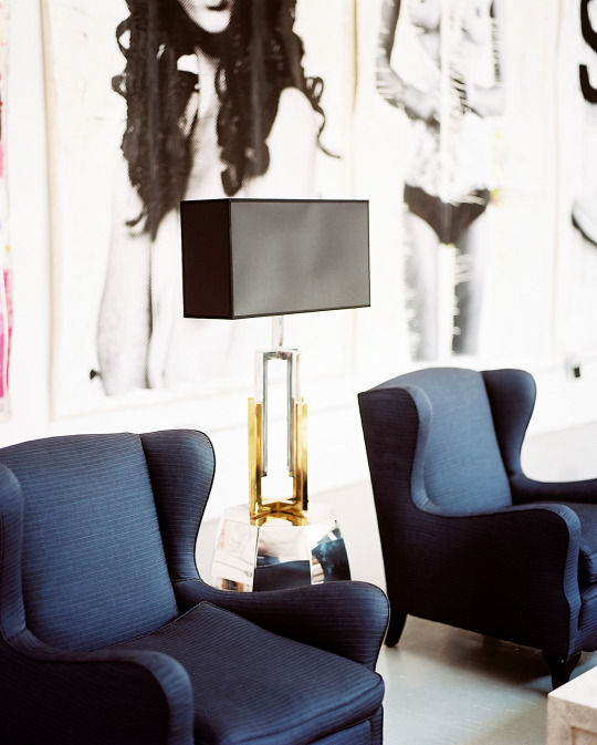 Pair of Navy Blue Statement Armchairs in Living Room with Hanging Nude Photographs.