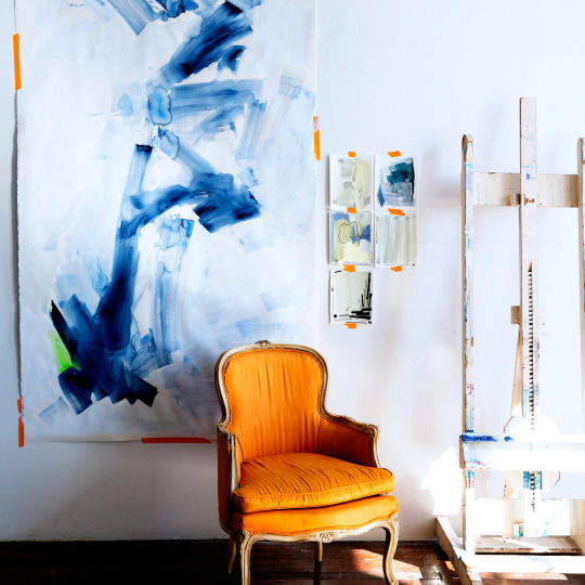 Orange armchair in front of abstract painting