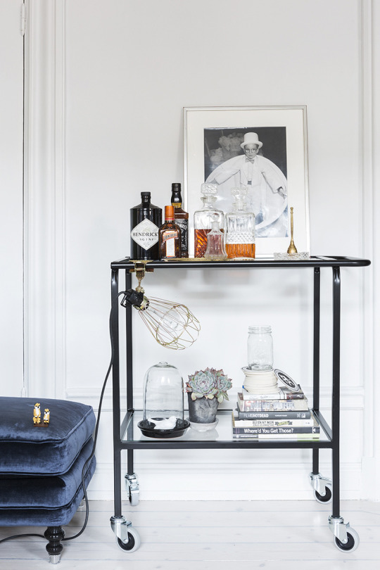 A simple black bar cart against a white wall