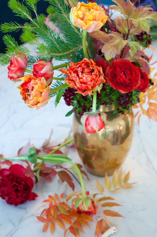 Red and green holiday floral arrangement on table