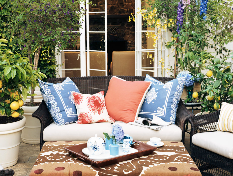 Outdoor Boho Patio with Numerous Orange and Blue Pillows and Suzani Covered Ottoman