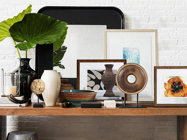Boho Chic Coffee Table With Decorative Wooden decor, Vintage Photographs, and a Large Mirror.