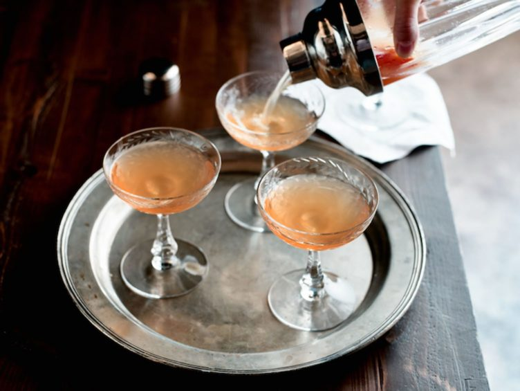 Vintage glasses on Silver Platter with cocktail being poured on Chairish.