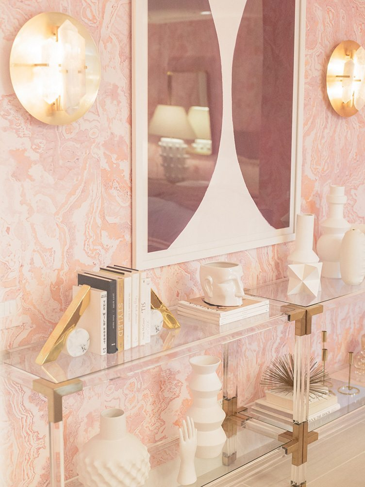 Assorted decor on clear, modern shelves, and abstract art in pink bedroom