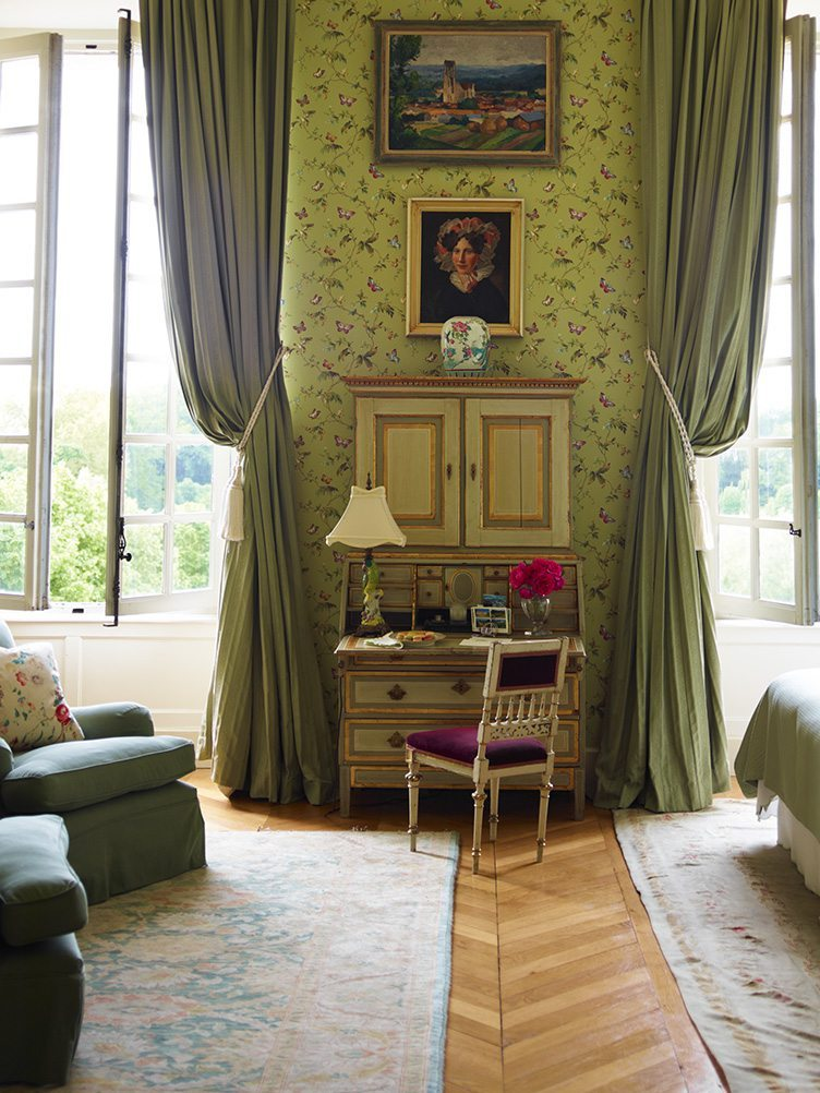 Traditional secretary desk in classic living room with a green color scheme and vintage art.