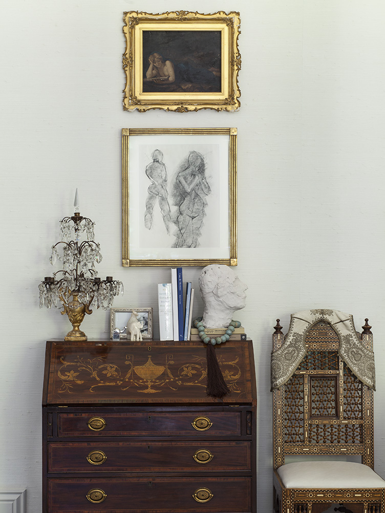 Ornate wooden hutch and chair agaist cream colored wall with framed wall art.