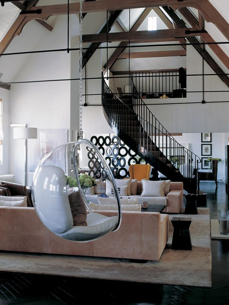 Contemporary modern living rooms with bubble chair and a large metal spiral staircase.