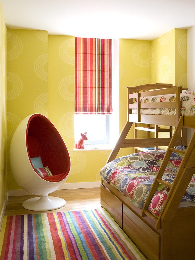 Fun egg chair in colorful children's bedroom with bright yellow wallpaper and bunkbeds.