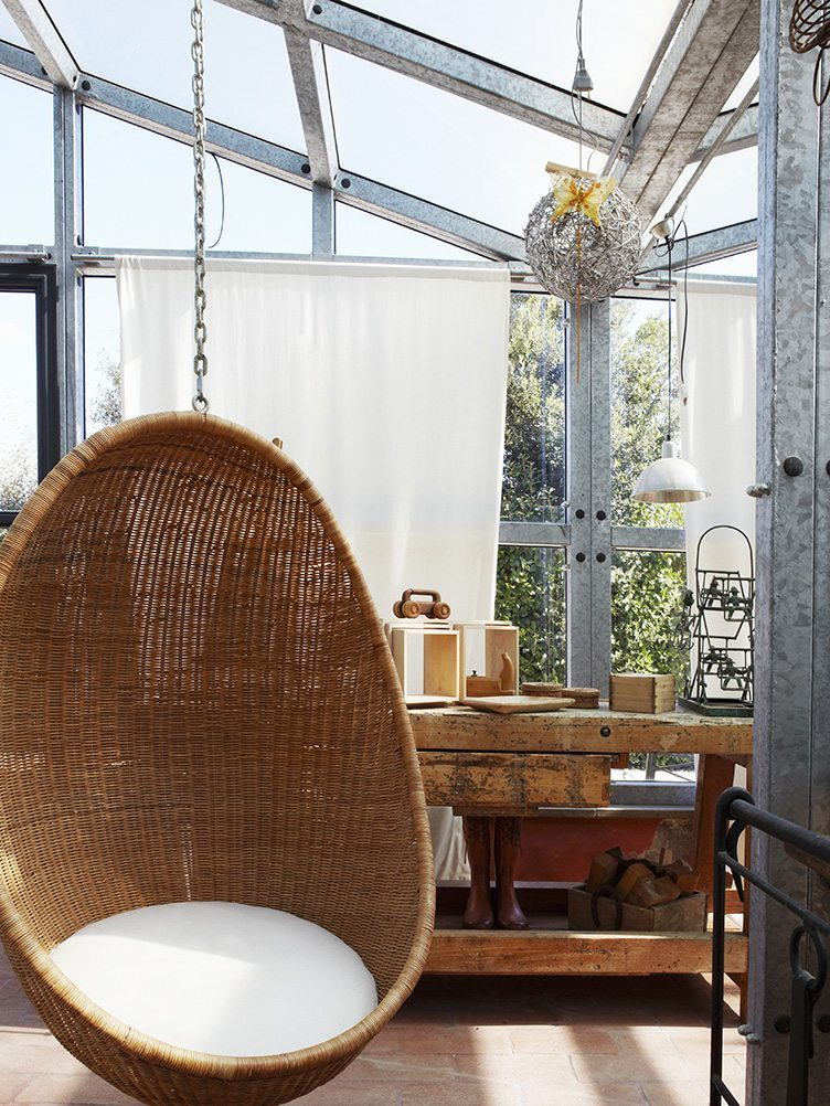 Comfortable, wicker hanging chair with white seat cushions and rustic workbench in conservatory.