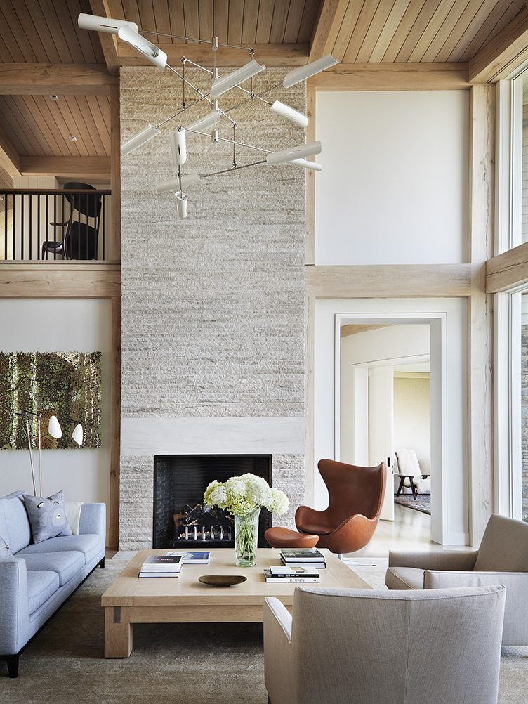 Contemporary living room with egg chair, wooden ceiling, and a large fireplace.