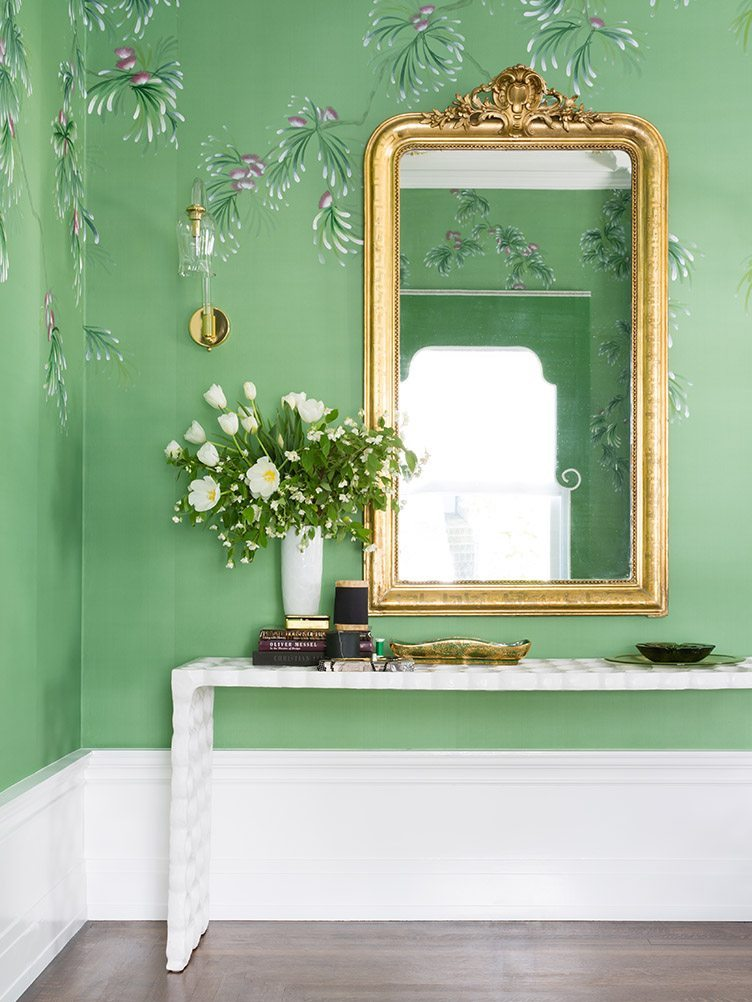 Modern white console table under gold-accented mirror against green wallpaper