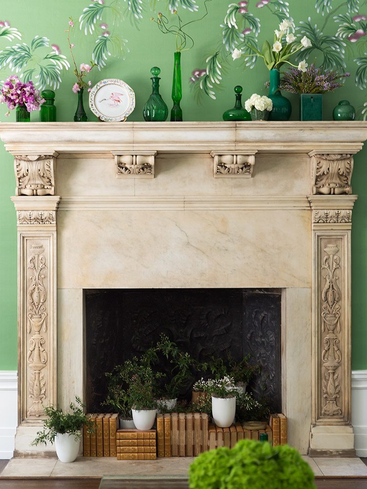 vintage glassware and books on tan fireplace mantel