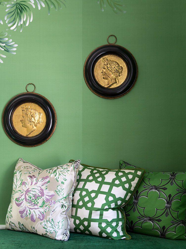 Green, patterned pillows against green wallpaper