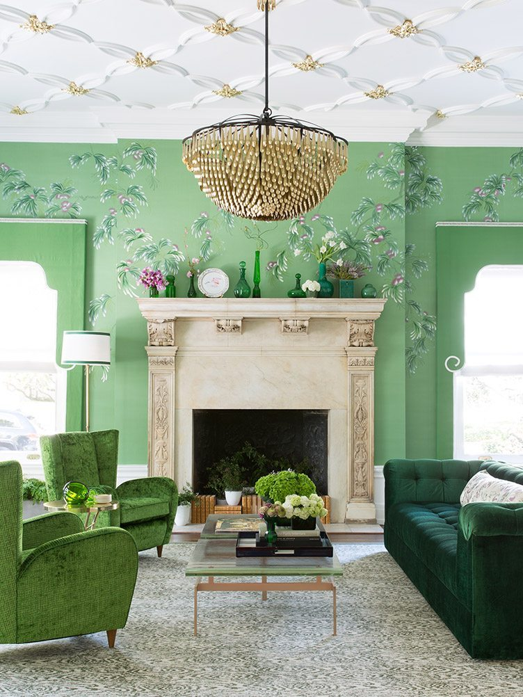 Green, velvet sofa, green loveseat, and tan, marble fireplace under gold  chandelier