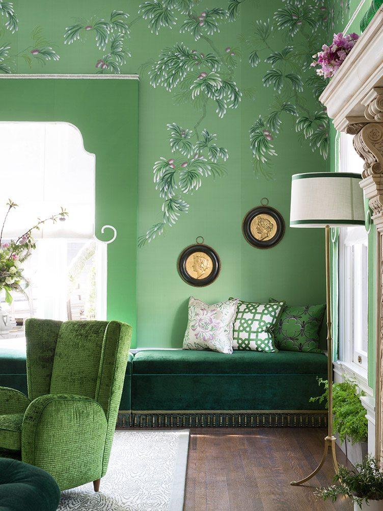 Green, velvet sectional, green loveseat, and tall lamp against green wallpaper