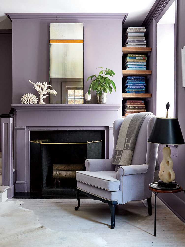 Lavender armchair, sculpted pearl lamp in front of lavender fireplace