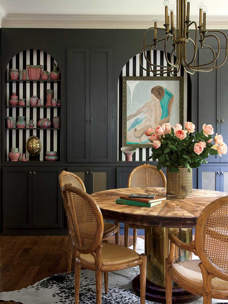 Woven dining chairs, chestnut dining table, impressionist painting in black dining room