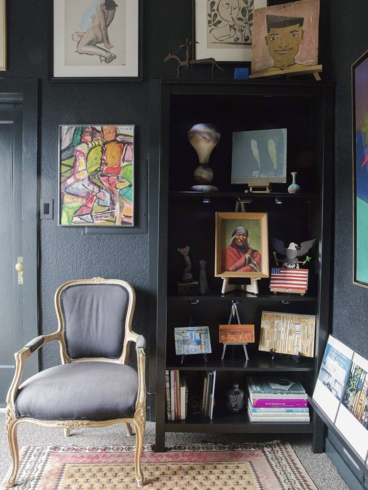 Home Gallery with Black Walls and Black Louis Chair Surrounded by Vintage Art.