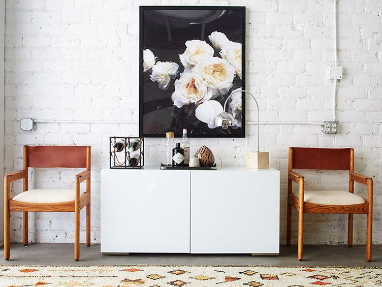 white flower art vintage woven rug cabinet wine serving tray chrome table lamp wood chairs brick wall
