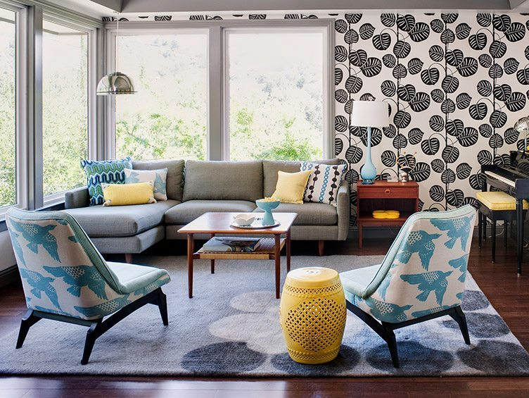 Bright contemporary living room with a pair of bird-patterned slipper chairs and black and white wallpaper.