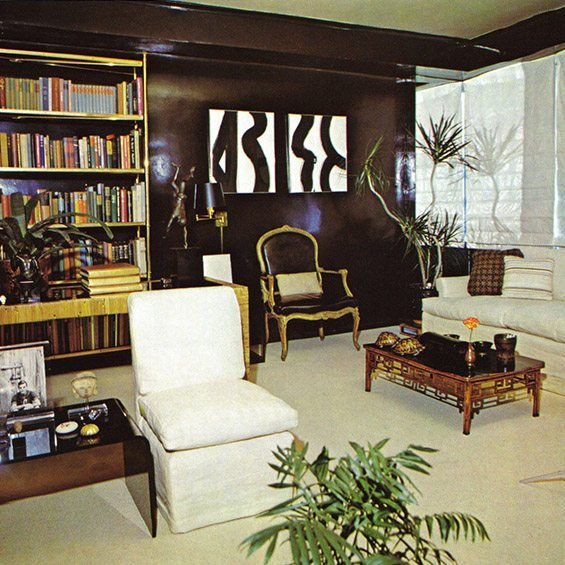 Beige slipper chair in traditional living room with large bookcase and dark walls.