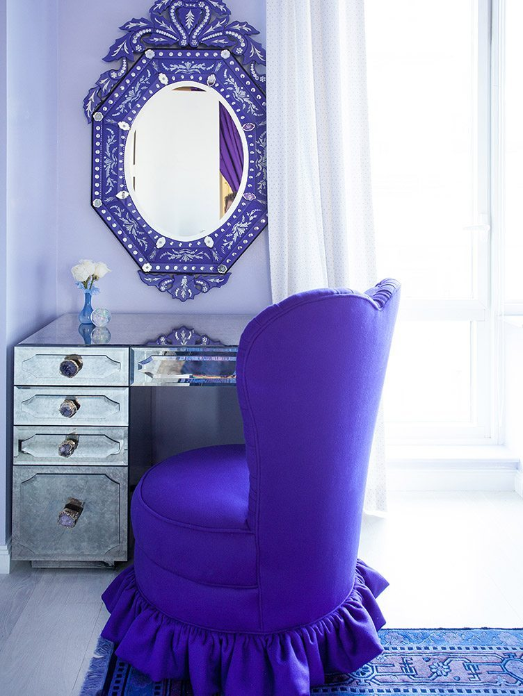 Glamorous workspace with a large purple mirror and a purple slipper chair.