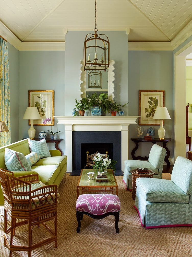 Bright beach house living room with a hanging chandelier and blue slipper chairs to match the blue walls.