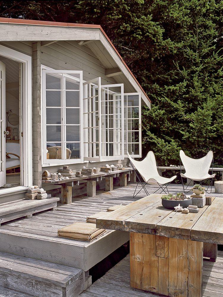 Two beige butterfly chairs on a rustic wooden outdoor porch.