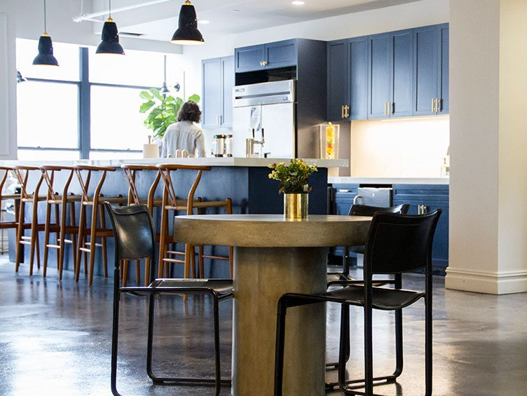 Contemporary Kitchen with Wooden Bar Stools and Navy Blue Cabinets and Appliances.