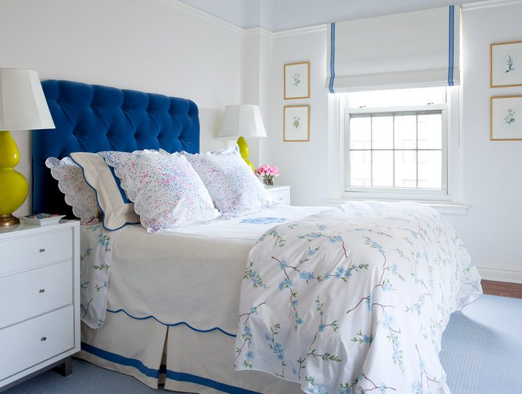 blue white bed sheets tufted headboard bedroom floral print pillows bedside tables scalloped edges