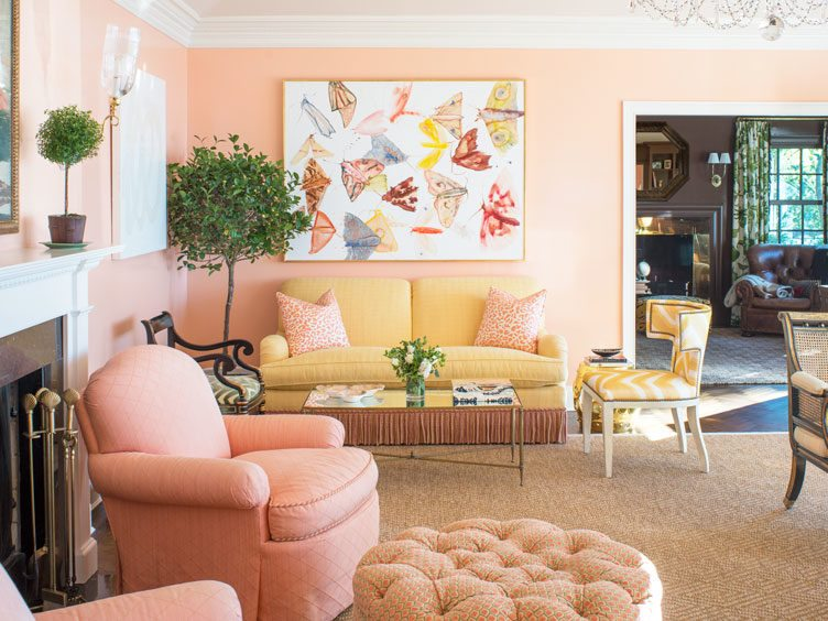 Yellow Tasseled Couch in Peach Colored Living Room with Large Butterfly Painting.