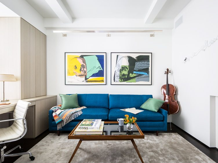 Contemporary Modern Living Room With Statement Blue Couch and Skull Pop Art