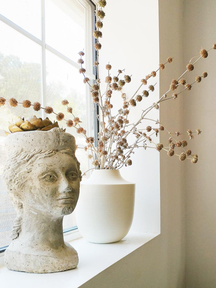 Stone Bust of Maiden Decorating Home Windowsill next to White Clay Pots.