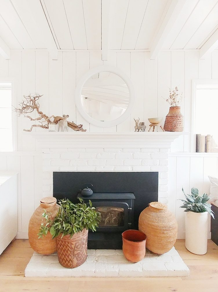 Rustic White Brick Fireplace Decorated with Handwoven Baskets and Plants.