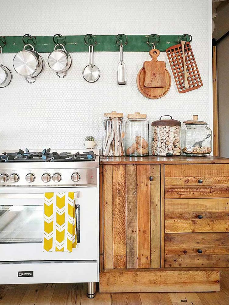 Rustic Kitchen with Green Hook Rack over Countertop and Oversized Glass Jar Containers.