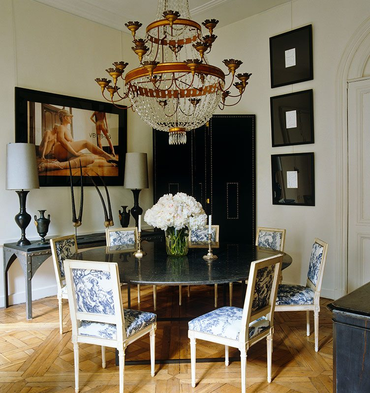 Traditional Dining Room With Large Crystal Chandelier and a Black Marble Table.