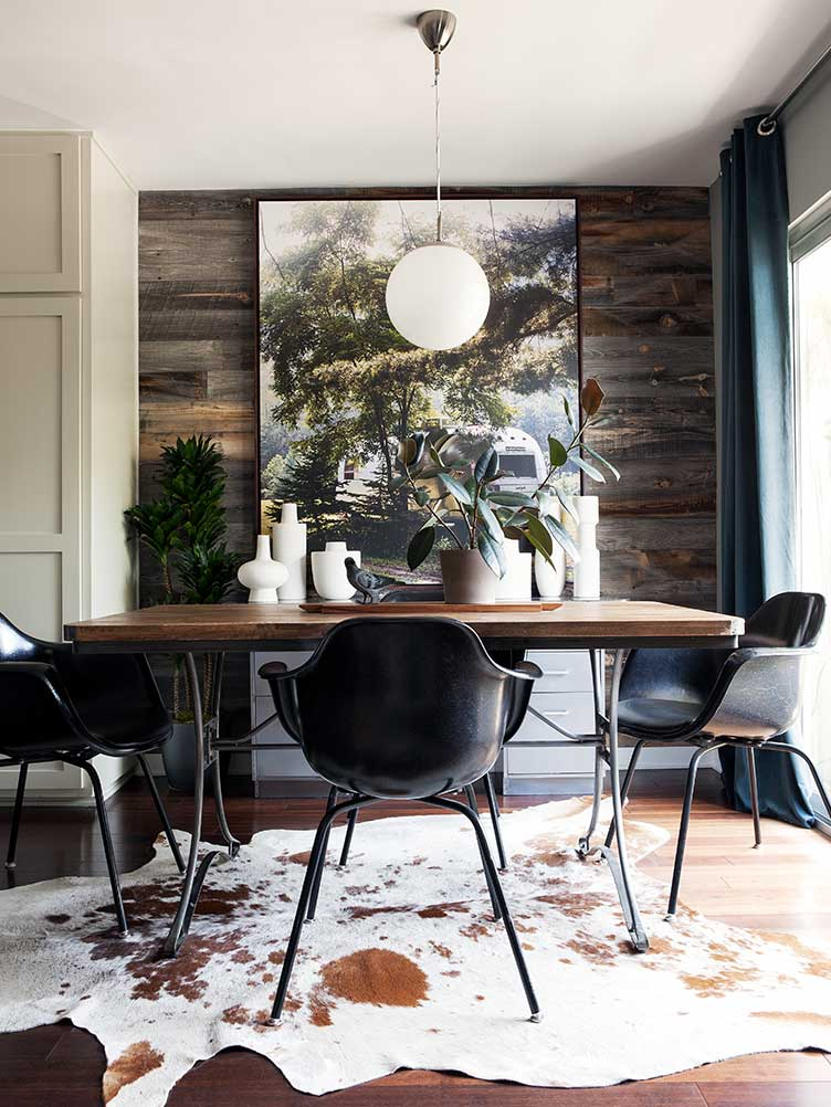 Rustic Modern Dining Room With Wooden Table And Black Chairs Over Cowhide  Rug.
