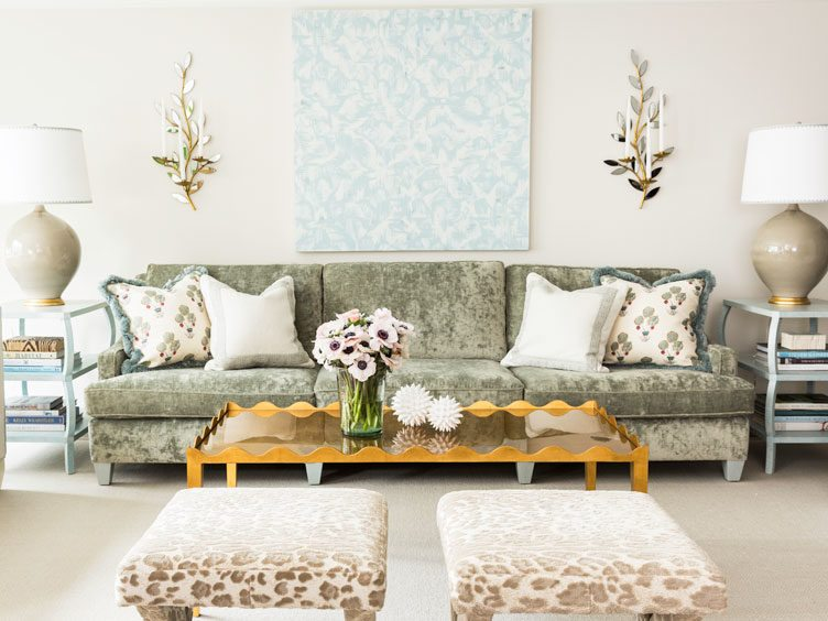 Sage sofa, cheetah print ottomans, twin blue accent tables, and eclectic orange coffee table in living room