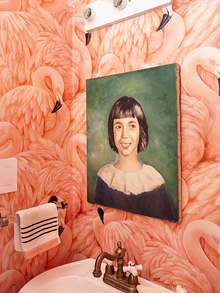 Bathroom with Pink Flamingo Wallpaper and Female Vintage Portrait Hanging over Sink.