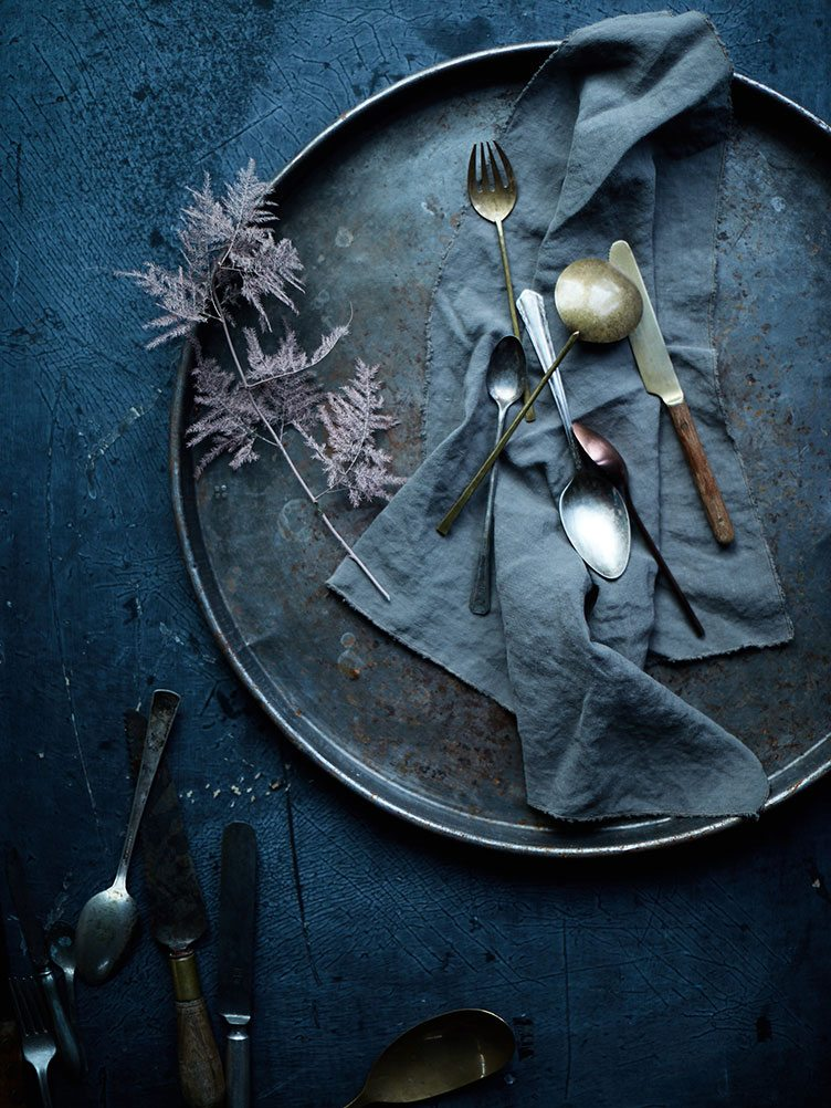 Silver and Bronze utensils lain across blue-grey cloth