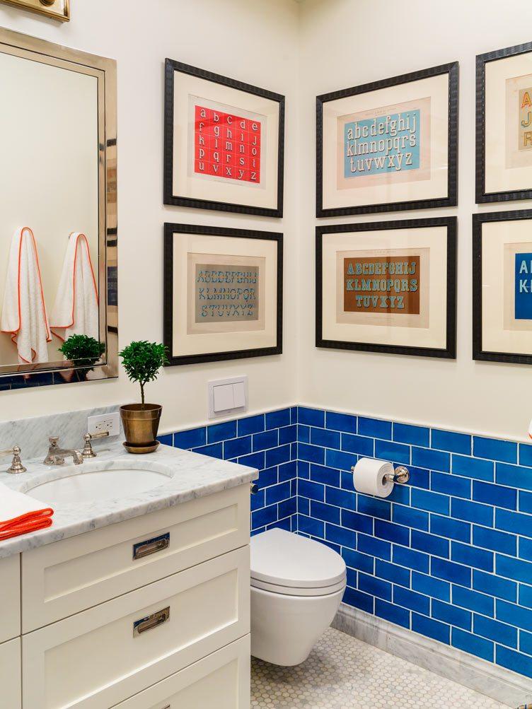 Tilton Fenwick interior design bathroom blue tiles white cabinets marble countertop wall art