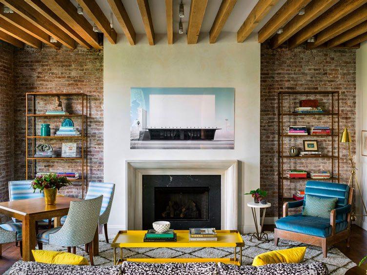 Tilton Fenwick interior design blue yellow pops color brick wall white black fireplace living room
