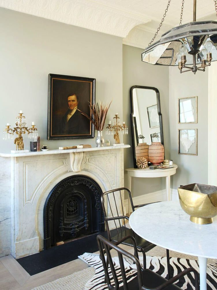 Traditional Marble Fireplace with Gold Candleholders and Vintage Hanging Portrait.