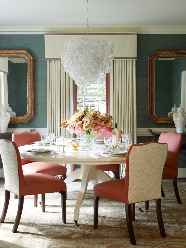 Traditional Dining Room Table with Pink Leather Dining Chairs and Large Glass Chandelier.